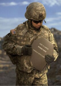 U.S. Army soldier in tan and green fatigues holding ceramic plate used in body armor